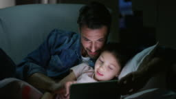 Portrait of happy father and daughter using a tablet on sofa in the evening in slow motion.