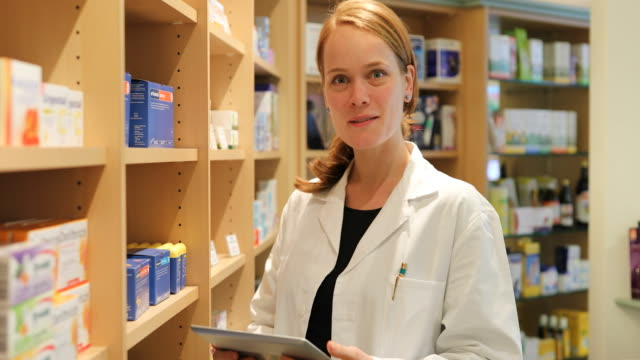 portrait of happy female pharmacist in store - one mid adult woman only stock videos & royalty-free footage