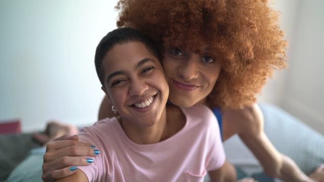 porträtt av lyckliga vänner / par avkopplande i sängen hemma - blandat ursprung bildbanksvideor och videomaterial från bakom kulisserna