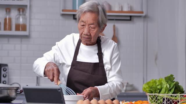 vídeos de stock, filmes e b-roll de retrato da avó feliz de 83 anos vestida usando avental marrom no visual moderno da cozinha receita online aprendendo em tablet digital e cozinhando refeição saudável. conceito de tecnologia em saúde sênior. - portable information device