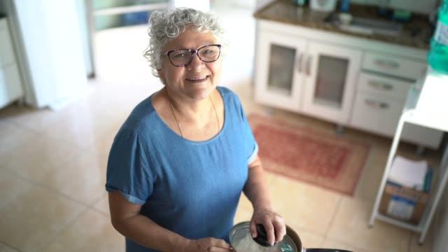 vídeos de stock, filmes e b-roll de retrato da avó feliz preparando almoço em casa - cozinhar