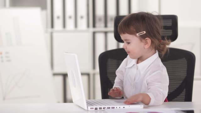 vídeos y material grabado en eventos de stock de hd: retrato de niña feliz con la computadora portátil - curiosidad