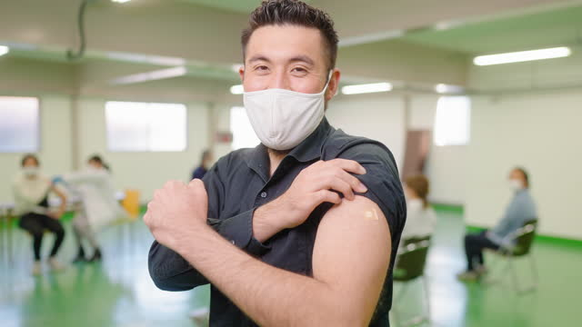 portrait of happy man showing his arm and smiling for camera after getting vaccinated - plaster stock videos & royalty-free footage
