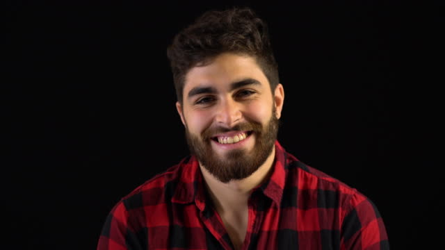 vídeos y material grabado en eventos de stock de retrato de feliz hombre con barba en la camisa roja - fondo negro