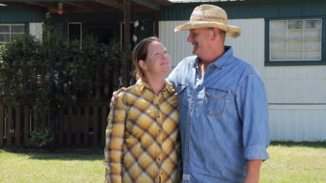 MS Portrait of happy mature couple in front of farm house / Madison, Florida, USA