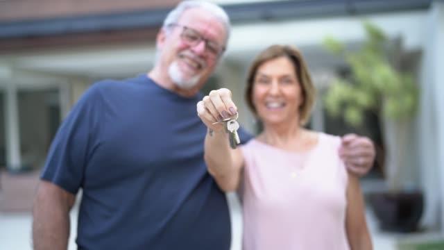 vidéos et rushes de portrait de couple mûr heureux montrant les clefs de leur nouvelle maison - devant