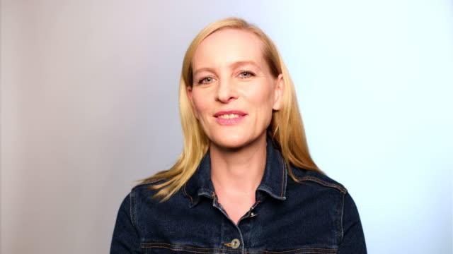 stockvideo's en b-roll-footage met portret van gelukkige volwassen vrouw met blond haar - formeel portret
