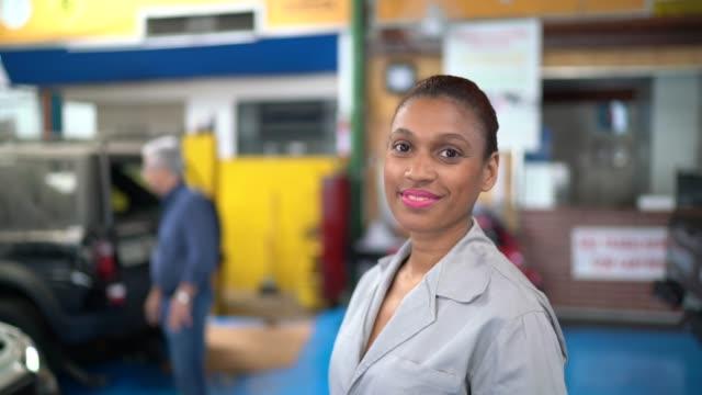 portrait of happy mechanic woman working in car repair shop - mechanic stock videos & royalty-free footage