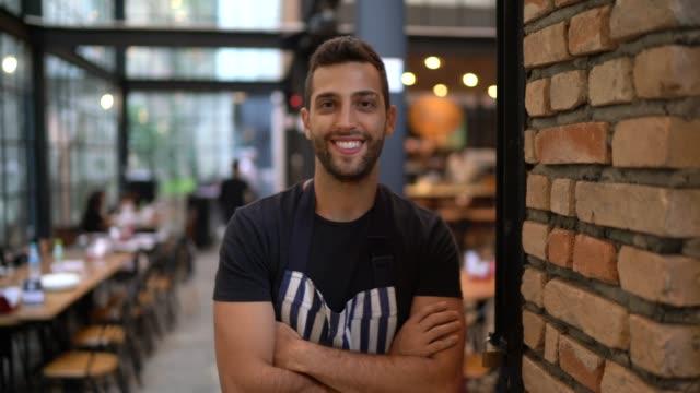 vídeos de stock e filmes b-roll de portrait of happy restaurant owner with arms crossed - empregado de mesa