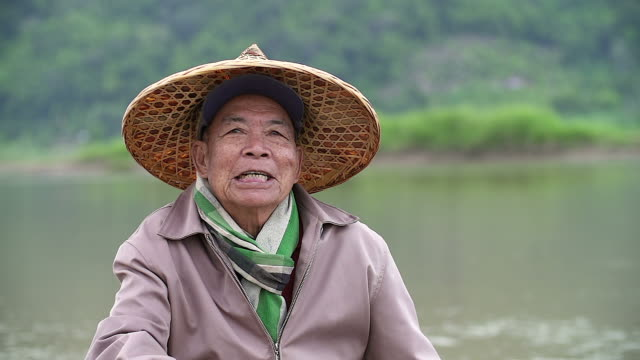 portrait of happy senior asian fisherman with a smiley face sitting near the river. - cambodia stock videos and b-roll footage