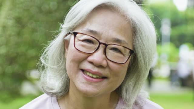 portrait of happy senior asian woman at park - taipei stock videos & royalty-free footage
