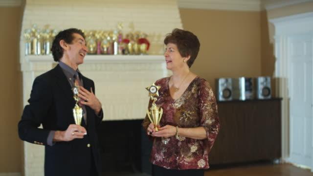 MS, Portrait of happy senior couple with trophies in dance studio, Hingham, Massachusetts, USA