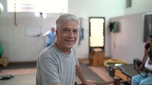 vídeos y material grabado en eventos de stock de retrato de un hombre de último año feliz en la clínica de fisioterapia - fisioterapia deportiva
