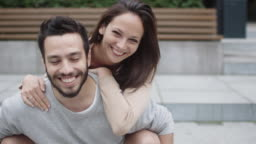 Portrait of Happy Smiling Couple Outdoors. Young Woman Hugging the Man