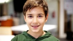 portrait of happy smiling preteen boy face at school classroom
