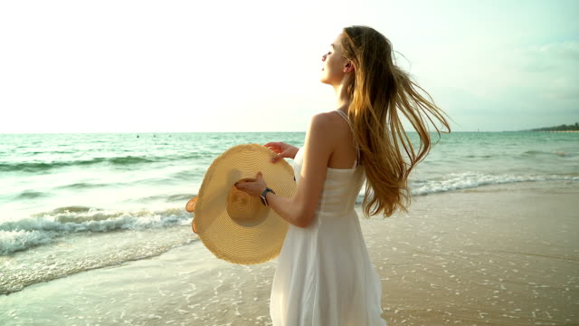 portrait of happy smiling woman on the beach. smiling sensual blonde posing on a beautiful wild beach. pretty girl in casual looking away during sunset. - dress stock videos & royalty-free footage