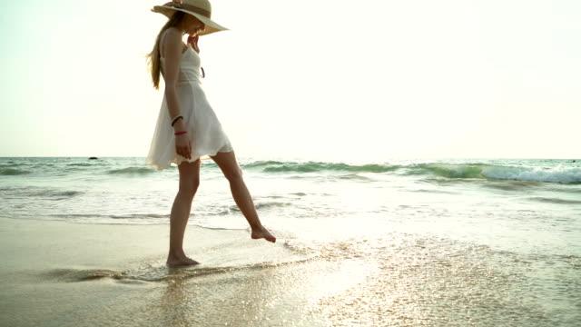 Portrait de femme souriante heureuse sur la plage. Le sourire sensuelle blonde posant sur une belle plage sauvage. Jolie fille en casual vous cherchez loin pendant le coucher du soleil.