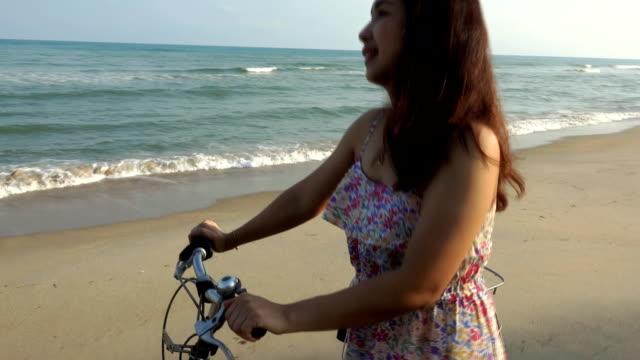 vídeos de stock, filmes e b-roll de retrato da mulher de sorriso feliz que anda com uma bicicleta na praia. - braço humano