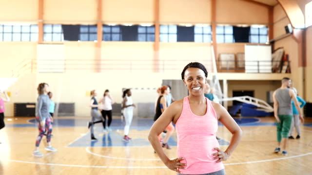 vídeos y material grabado en eventos de stock de retrato de feliz mujer joven sonriente en el gimnasio - adulto de mediana edad