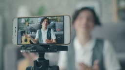 Portrait of happy teen recording video vlog with smartphone talking gesturing