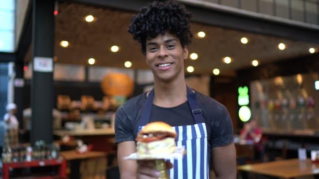 portrait of happy waiter holding a tasty burger - pardo brazilian stock videos & royalty-free footage