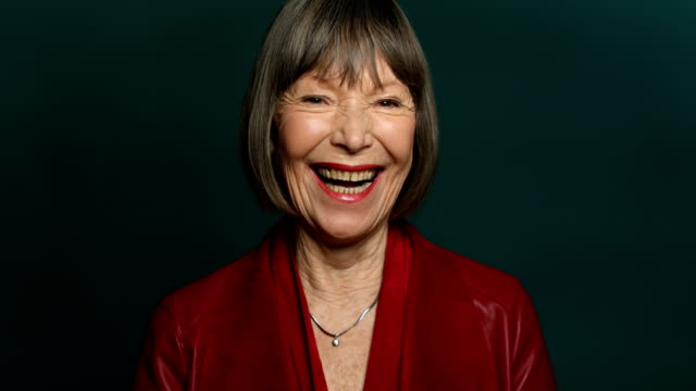 portrait of happy woman against green background - senior women stock videos & royalty-free footage