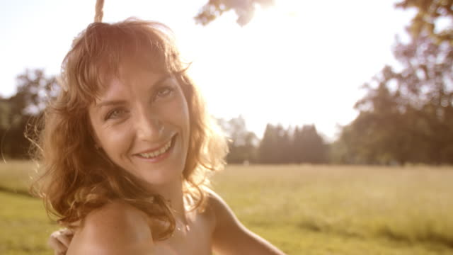 slo mo ritratto di felice donna su un altalena - solo ragazze video stock e b–roll