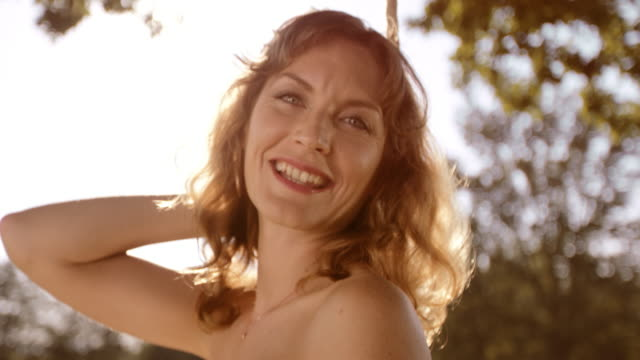 SLO MO Portrait of happy woman swinging in sunshine