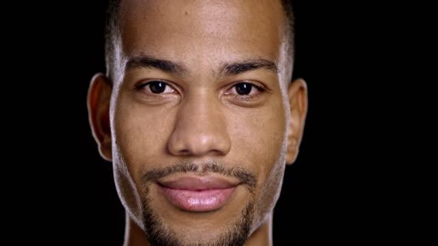 vídeos de stock, filmes e b-roll de retrato de jovem feliz homem afro-americano - fundo preto
