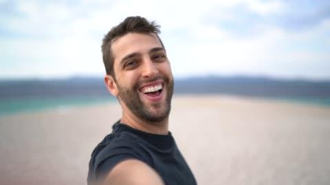 vídeos de stock e filmes b-roll de portrait of happy young man taking a selfie at the beach - young men