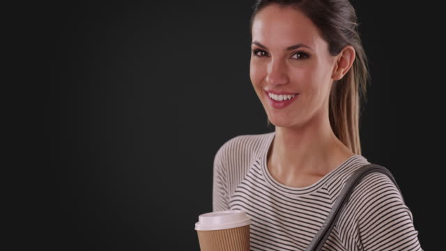 vídeos de stock e filmes b-roll de portrait of happy young white woman holding coffee on dark gray background - cabelo natural