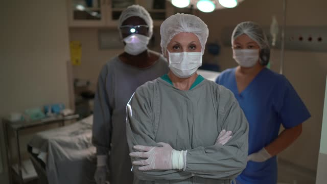 vídeos de stock, filmes e b-roll de retrato de colegas de saúde com máscara facial na sala de cirurgia do hospital - braços cruzados