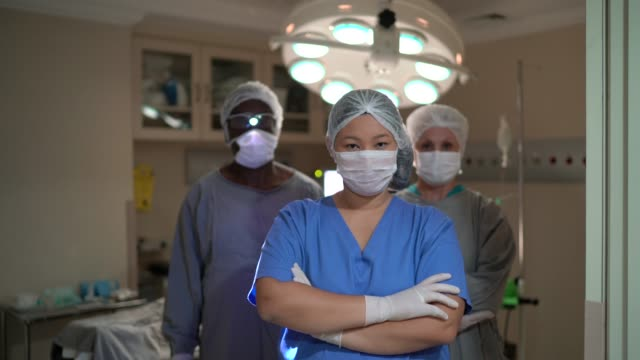 vídeos de stock e filmes b-roll de portrait of healthcare coworkers with face mask on operating room at hospital - cirurgião