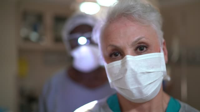 portrait of healthcare coworkers with face mask on operating room at hospital - gender equality stock videos & royalty-free footage