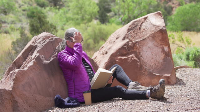 portrait of healthy senior woman having time to herself to read outdoors - letteratura video stock e b–roll