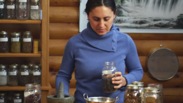 MS Portrait of herbalist grinding herbs in mortar and pestle in shop / Manchester, Vermont, USA