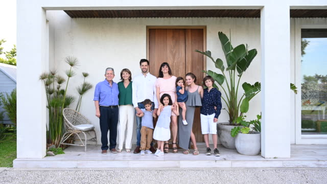 portrait of hispanic family in front of modern home - mid distance stock videos & royalty-free footage