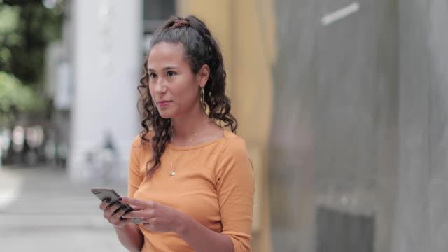 vídeos de stock, filmes e b-roll de portrait of hispanic young adult female using smartphone on busy city street - estudante universitária