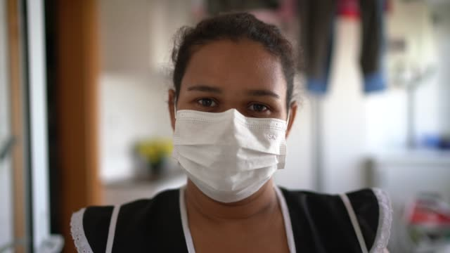 portrait of housekeeper wearing protective mask at house - prevenzione delle malattie video stock e b–roll