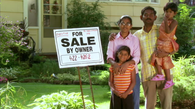 ms portrait of indian family with two daughters (2-3, 6-7) standing in front of house at 'for sale' sign, halifax, nova scotia, canada - see other clips from this shoot 1464 stock videos and b-roll footage
