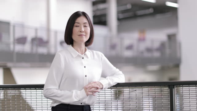 portrait of japanese businesswoman in corporate office - looking at camera点の映像素材/bロール