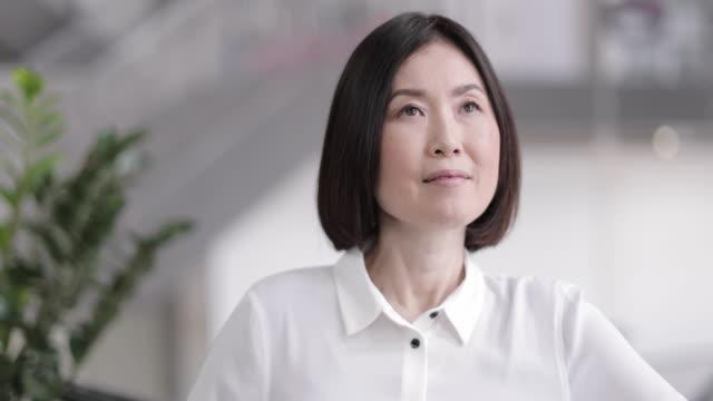 portrait of japanese businesswoman in corporate office - ホワイトカラー点の映像素材/bロール