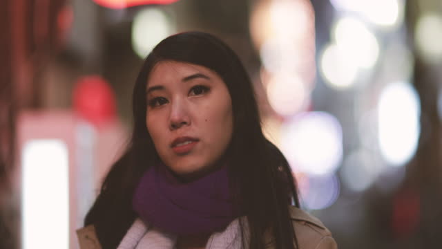 portrait of japanese female on street in shinjuku at night, tokyo, japan - 立つ点の映像素材/bロール