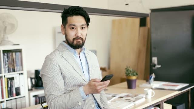 Porträt von japanischen Grafik-Designer mit einem Smartphone