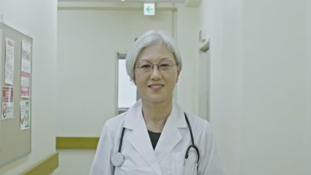 portrait of japanese senior female doctor walking at hospital corridor - professor stock videos & royalty-free footage