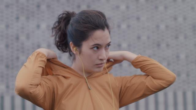 vídeos y material grabado en eventos de stock de portrait of japanese woman in sports clothing putting in headphones, zipping up jacket in tokyo, japan. - capucha