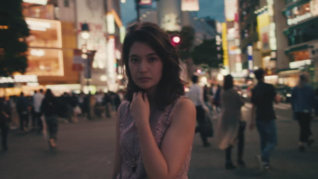 portrait of japanese woman in the middle of busy intersection at night / tokyo, japan - zebra crossing stock videos & royalty-free footage