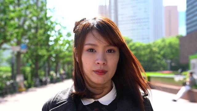vídeos de stock, filmes e b-roll de retrato da mulher japonesa sorrindo para a câmera com construção como pano de fundo da cidade. - japonês