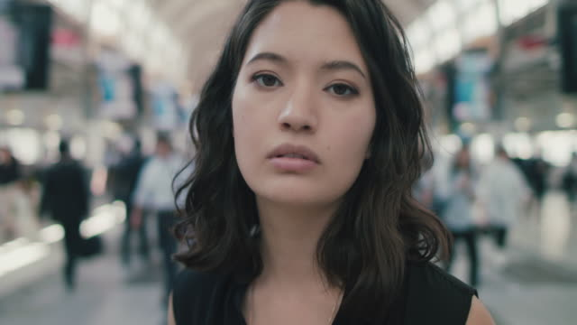 portrait of japanese woman standing in busy train station in tokyo, japan - geschäftsreise stock-videos und b-roll-filmmaterial