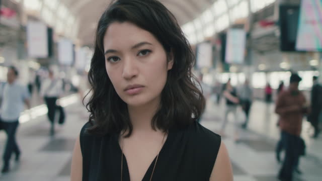 portrait of japanese woman standing in busy train station in tokyo, japan - 心の平穏点の映像素材/bロール